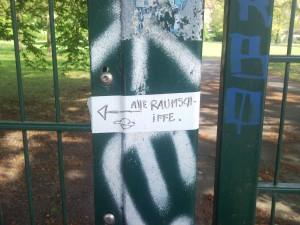 Zaun zum Prinzenbad: Auf einem Zaunpfahl ein Aufkleber, handgeschrieben steht dort: Alle Raumschiffe, Pfeil nach links