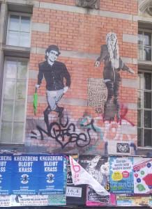 """zuplakatierte Häuserwand, auf einigen Plakaten steht """"Kreuzberg bleibt krass"""", darüber street art paste ups, die lebensgrosse tanzende Hipster zeigen"""