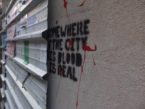 Graffiti in Tel Aviv, halb hinter einer Wellbleckabdeckung: Somewhere in the city this blood is real