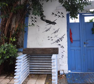 Blaue Tür, daneben eine weisse Wand mit paste ups: Mehere Flugzeugstaffeln und Fallschirme (Tel Aviv)