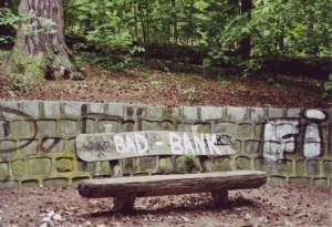 """Eine halbverrottete Holzbank an der Krummen Lanke, mit weißer Farbe wurde auf die Rückenlehne """"Bad Bank"""" geschrieben"""