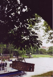 Blick auf den Kanal, im Vordergrund hängt ein Obstholzkorb von einem Baum, darauf steht: Flaschensammelkorb / Bottle-Collecting-Box, im Hintergrund ein Boot der Wasserschutzpolizei
