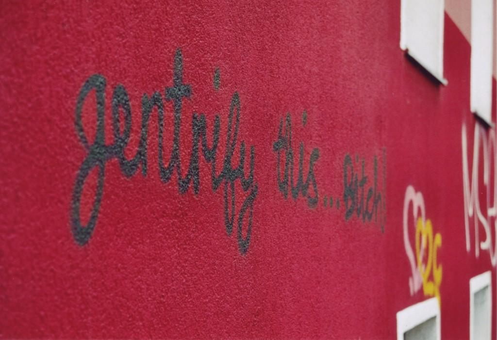 Graffiti auf einer frisch gestrichenen roten Wand: gentrifiy this...Bitch!