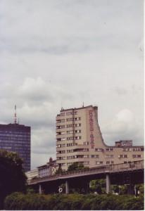 Ein Haus ragt hinter dem Hochbahnviadukt in die Höhe, bedeckt von Graffiti
