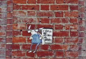 Street Art paste up auf einer Backsteinmauer: Eine Comicfigur, vielleicht ein Hase, mit Brille und Hose bis unters Kinn, Sprechblase: Je höher die Hose desto hipper der Hipster