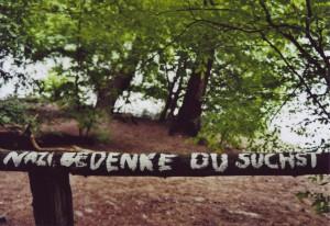 """Ein Holz-Geländer an der Krummen Lanke, mit weißer Farbe beschrieben: Nazi, bedenke du suchst..."""""""