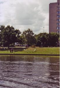 Blick über den Kanal zum Urban, auf der Wiese davor eine Installation aus herabstürzenden Flugzeugen