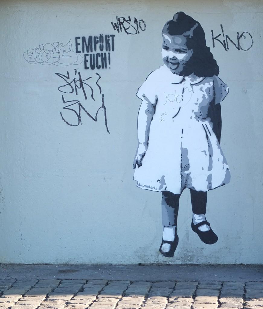 Street Art Bild: Ein kleines Mädchen streckt die Zunge raus, daneben ein Graffiti: Empört Euch!