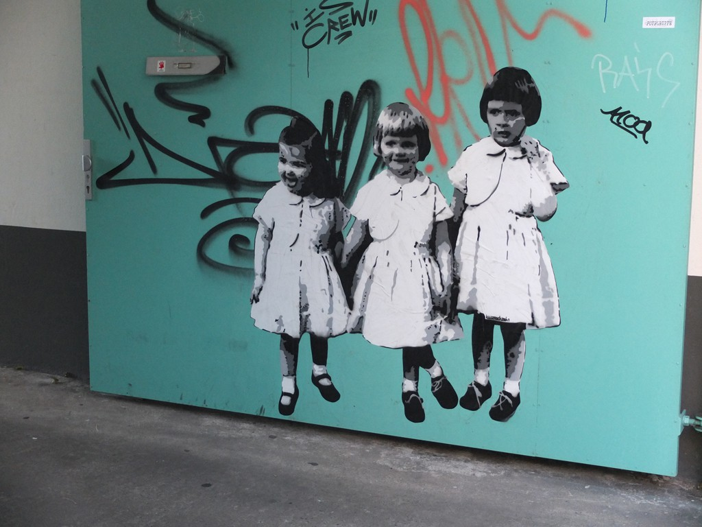 Street Art: drei junge Mädchen in Kleidern stehen nebeneinander wie die Orgelpfeifen