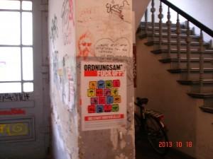 Ein Hausflur mit vielen Graffitis und einem Plakat: Ordnungsamt Fuck off