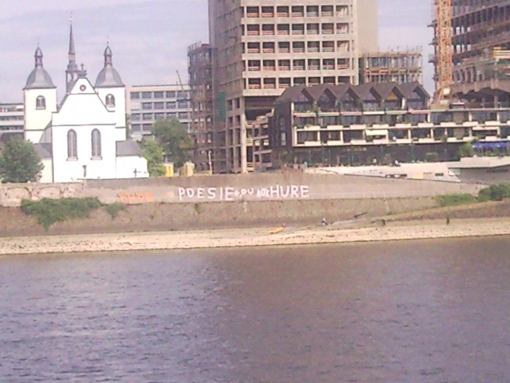 """Rheinufer in Köln, an der Mauer gegenüber ist schwach der Schriftzug """"Poesie du alte Hure"""" zu erkennen"""