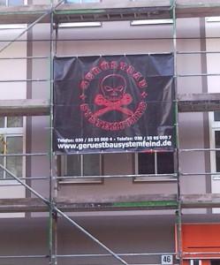 Werbebanner an einem Gerüst: Gerüstbau Systemfeind, dazu als Logo ein Totenkopf