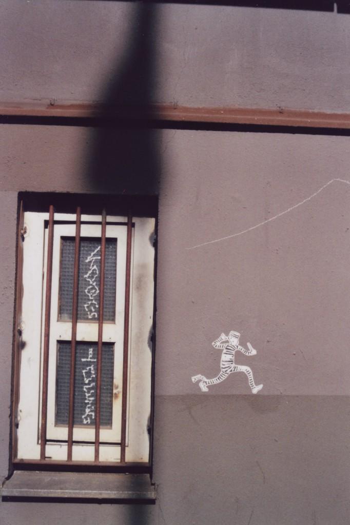Street Art Paste Up: Ein Comicmännchen mit gestreifter Sträflingskleidung rennt weg von einem vergitterten Fenster und zeigt diesem eine lange Nase