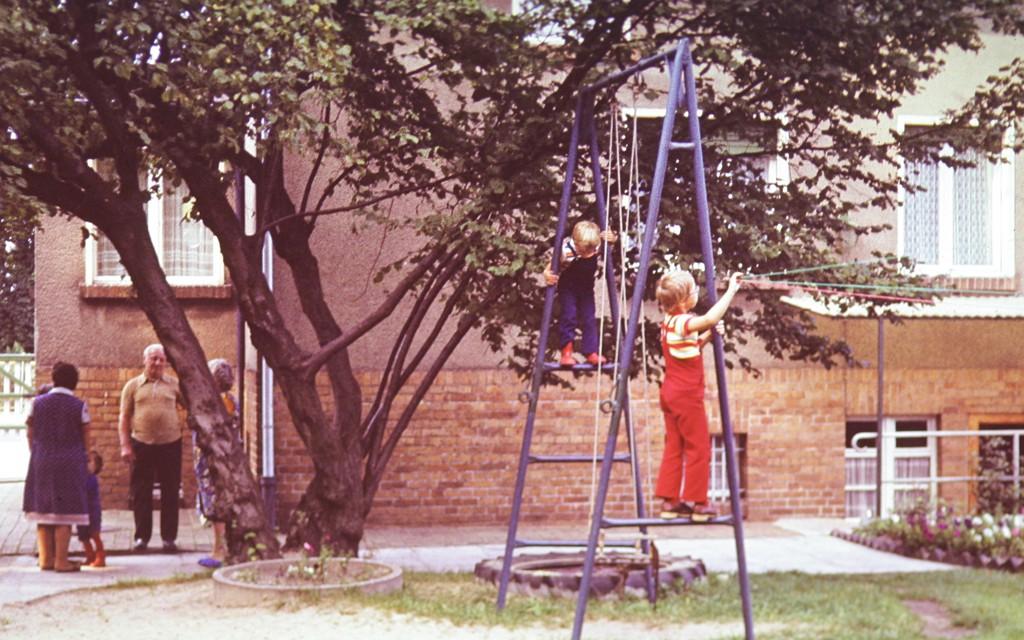 Ein Haus, vom Hof aus gesehen, davor ein Haselnussbaum, davor eine Schaukel auf der zwei Kinder klettern