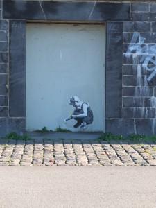 Street Art: Ein junges Mädchen sitzt in der Hocke und pflückt eine Blume