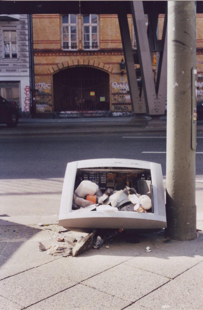 Ein alter Röhrenfernseher liegt neben einer Strassenlaterne, die Röhre ist zerbrochen und im so entstehenden Hohlraum hat sich einiger Unrat angesammelt