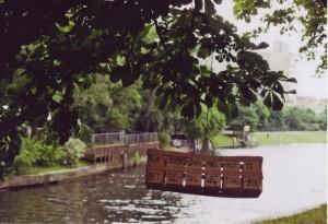 Blick auf den Kanal, im Vordergrund hängt ein Obstholzkorb von einem Baum, darauf steht: Flaschensammelkorb / Bottle-Collecting-Box