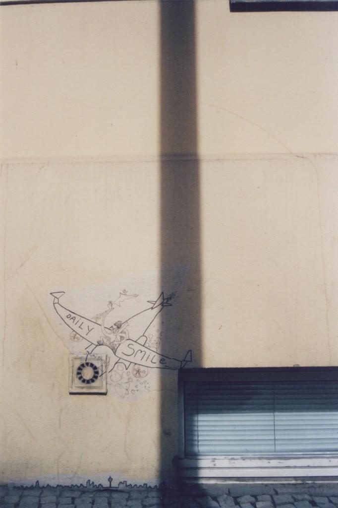 Street Art paste up: Ein Propellerflugzeug mit fröhlichem Piloten darin, der Propeller ist ein Lüftungsschacht o.ä. an der Hauswand