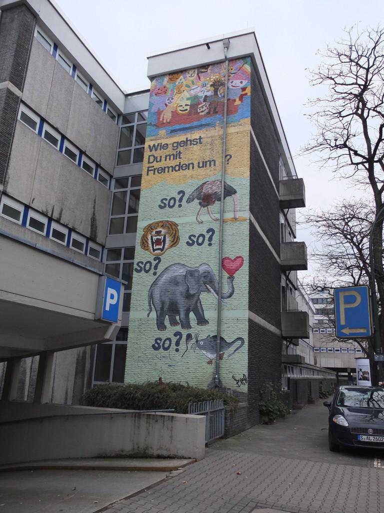 Bunte Fassadenmalerei an einer Schule: Wie gehst du mit Fremden um?