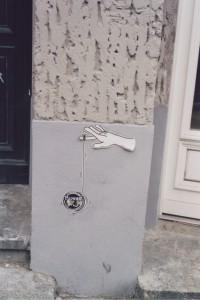 Street Art Paste Up: Eine Bewag-Plakette dient als Jojo, der von einer Hand/den Fingerspitzen gehalten und bewegt wird