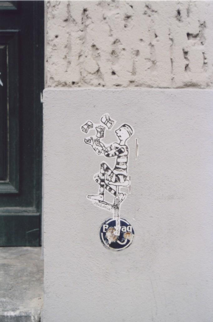 Street Art Paste Up: Diesmal dient die Bewag-Plakette als Einrag, auf der eine Art Comicclown jongliert