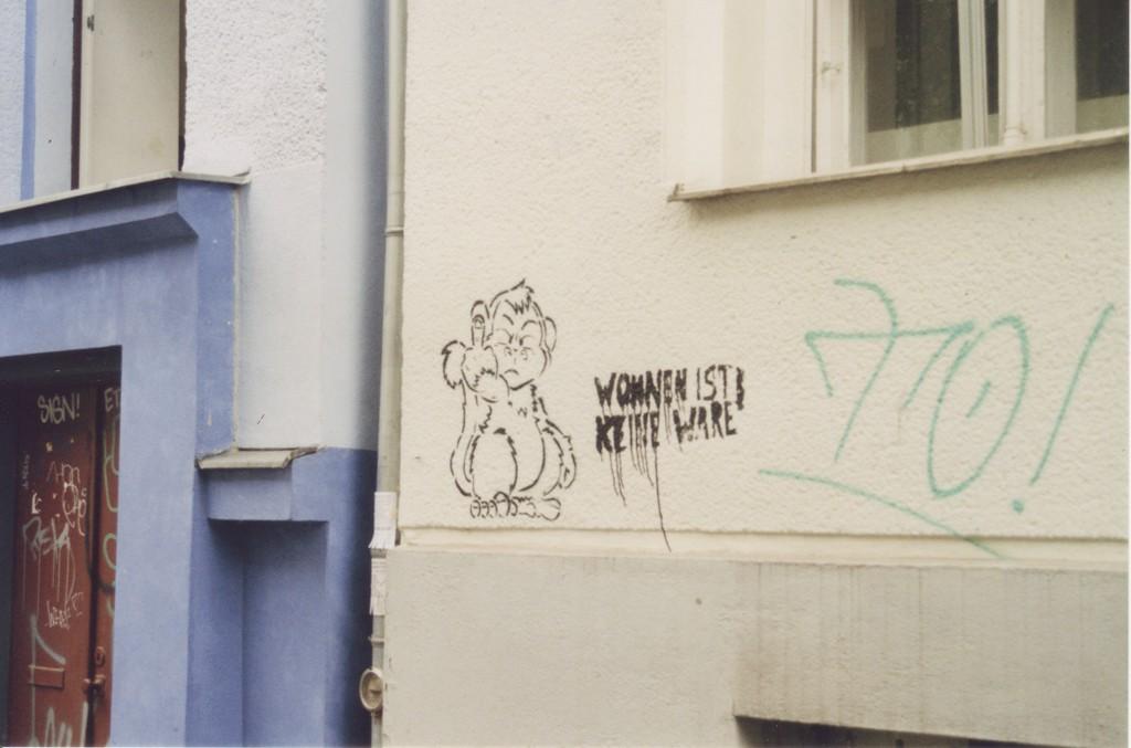 """Grafftiti an einer Häuserwand: Ein Affe, der grimmig den Mittelfinger zeigt, dazu der Schriftzug """"Wohnen ist keine Ware"""""""