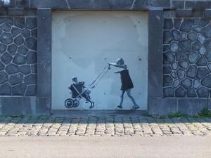 Street Art auf einer massiven Kasemattenmauer: Ein kleines Mädchen schiebt einen Puppen-Kinderwagen
