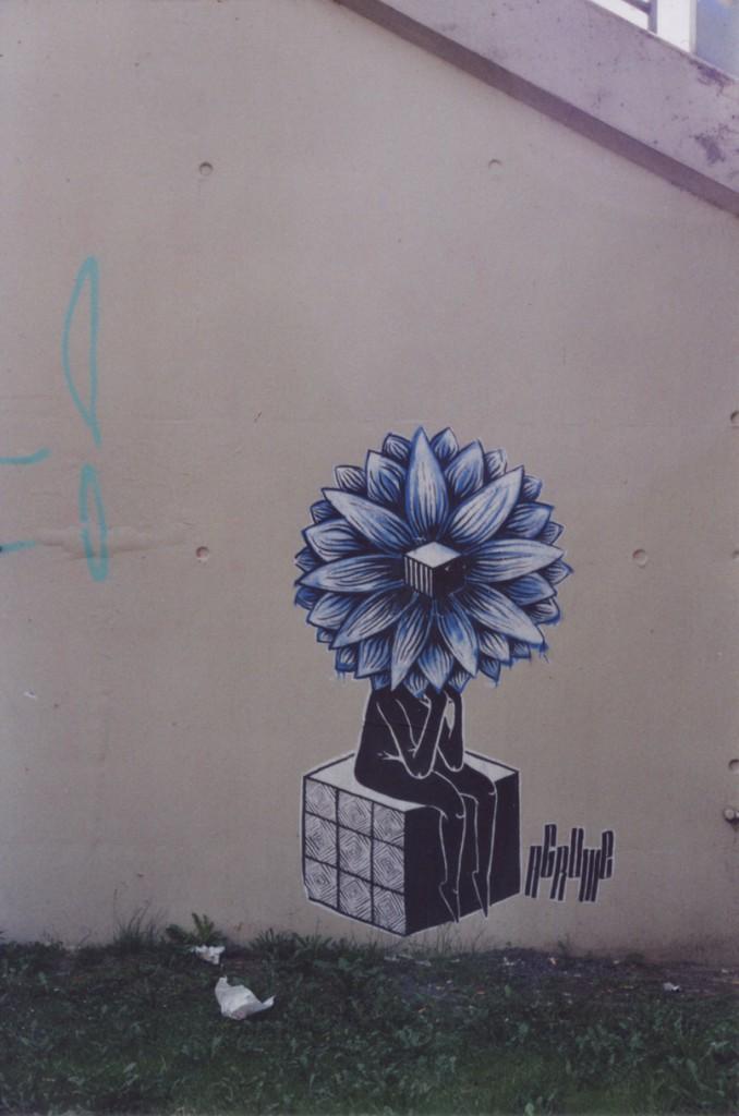 Street Art an einer Mauer: Eine auf einem Würfel sitzende Person, die als Kopf eine Art Blüte hat