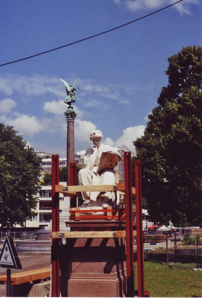 Sitzfigur Klio, Ferdinand Hartzer, Mehringplatz Berlin, die Figur ist von einem Baugerüst eingefasst