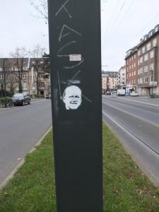 Street Art: Schablonenpostiv eines Gesichtes auf einem Strommast