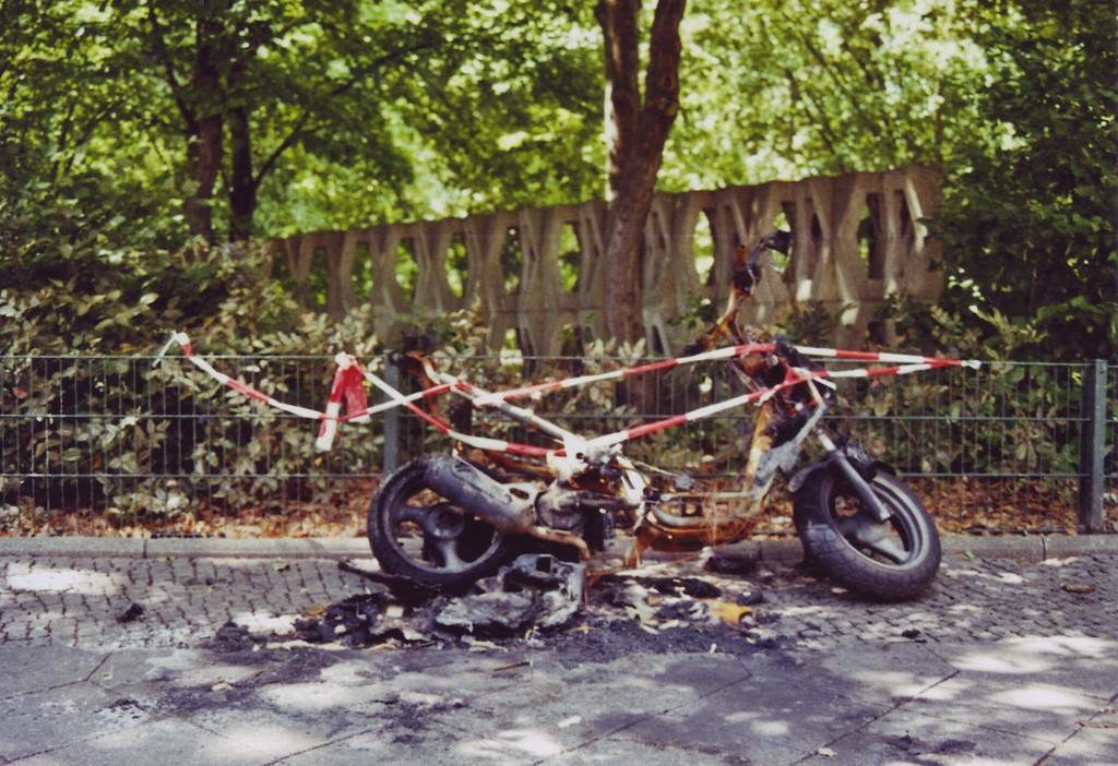Ein asugebranntes Moped, verkohlte Reste der Verkleidung und Absperr-Flatterband drum herum