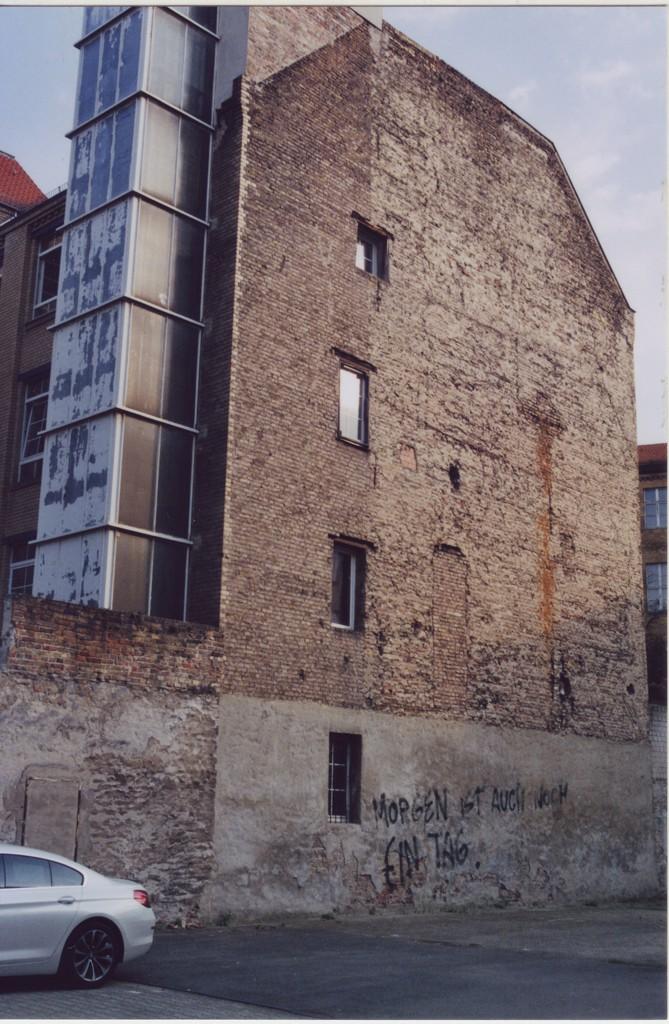 Eine beinahe fensterlose Wohnhausfassade, Brandwand, der Putz bröckelt ab, unten an der Wand ein Graffti: Morgen ist auch noch ein Tag