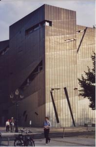 Fassade des von der Sonne angestrahlten Jüdischen Museums in Berlin, davor kreuzen einige Passanten die Strasse