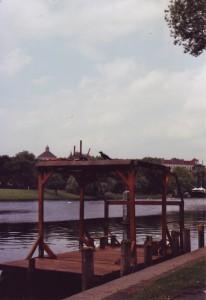 Ein Rabe sitzt auf dem Dach eines Flosses, das am Ufer des Landwehrkanals vertäut ist