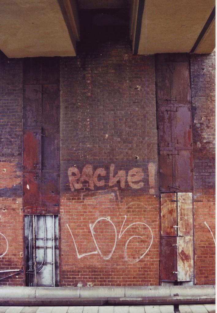 """Auf einer Backstein-Hausmauer (Gebäude auf dem Bahnsteig S-Bhf. Tempelhof) steht der Schriftzug """"Rache"""", aufgetragen mittels Säuberung oder Aussparung der betreffenden Stellen wie es scheint"""