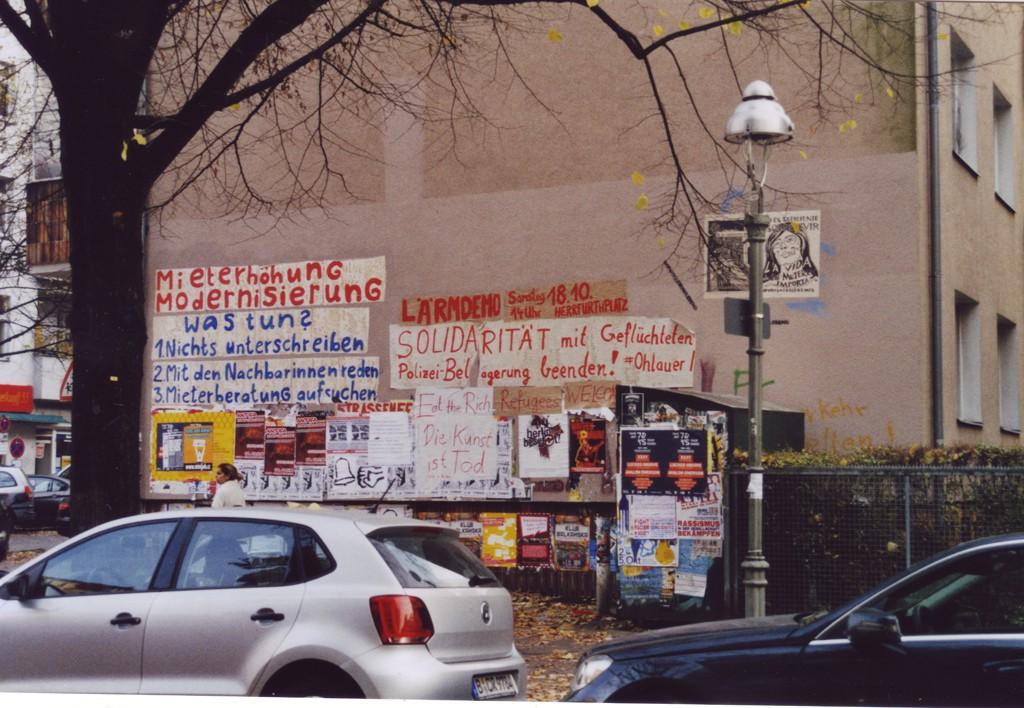 Brandmauer eines Wohnhauses, mit großen Schriftzügen plakatiert zu Mieterhöhungen und Modernisierung