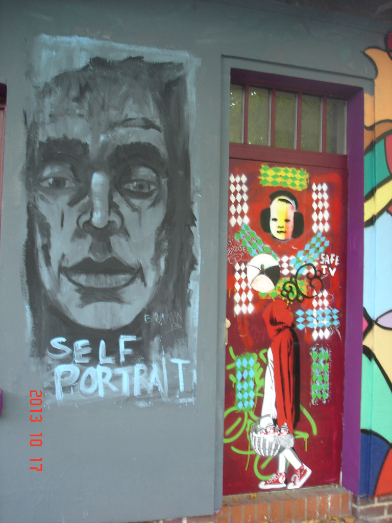 Fassade eines kleinen Hauses am Landwehrkanal, Nahaufnahme der Tür und der Wand daneben, beide mit Street Art Bildern verziert: Auf der Wand ein Gesicht mit dem Schriftzug Self Portrait drunter, auf der Tür eine Art Sprayer-Rotkäppchen mit dem Korb voller Farbdosen