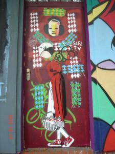 Detailaufnahme der Tür: eine Art Sprayer-Rotkäppchen mit dem Korb voller Farbdosen, darüber das Gesicht eines kleinen Kindes mit dicken Kopfhörern