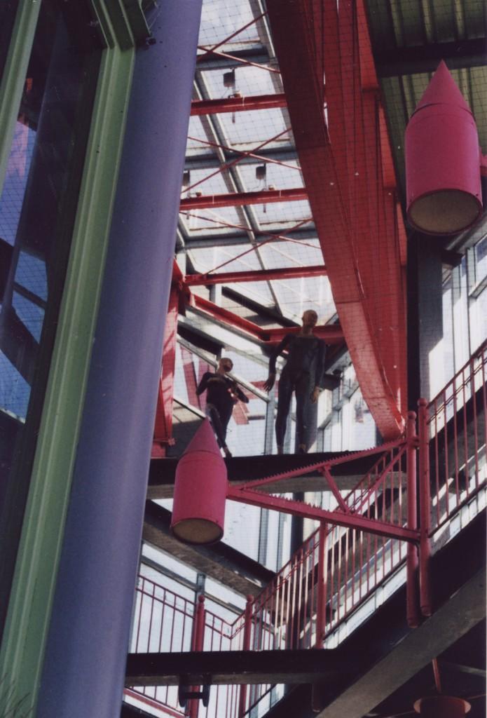 zwei Schaufensterpuppen stehen hoch oben in einem bunten, verwinkelten Glas-Stahl-Treppenaufgang