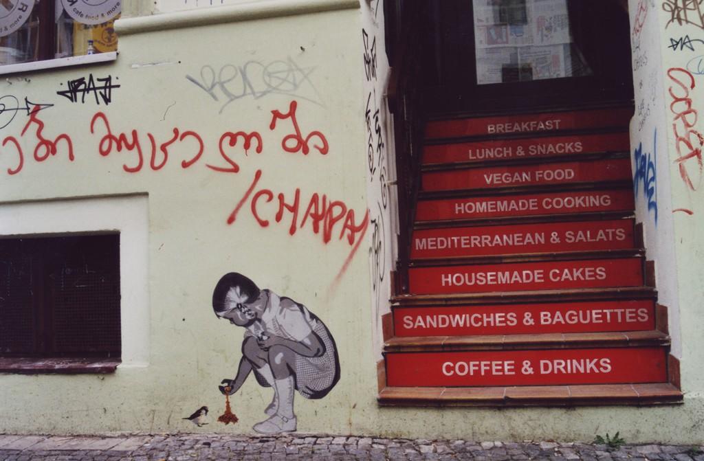 Street Art paste up eines kleinen Mädchens, das kniend eine Meise füttert, an einer Hauswand direkt neben einem Restauranteingang
