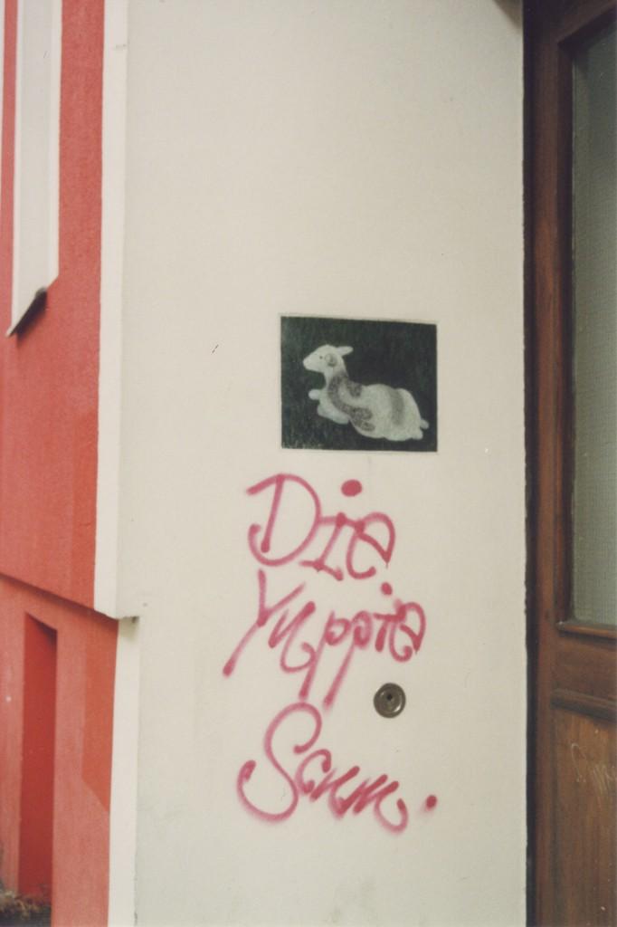 """Street Art in einem Hauseingang: Bild eines liegenden Schafes, darunter der Grafftiti-Schriftzug """"Die Yuppie Scum"""""""