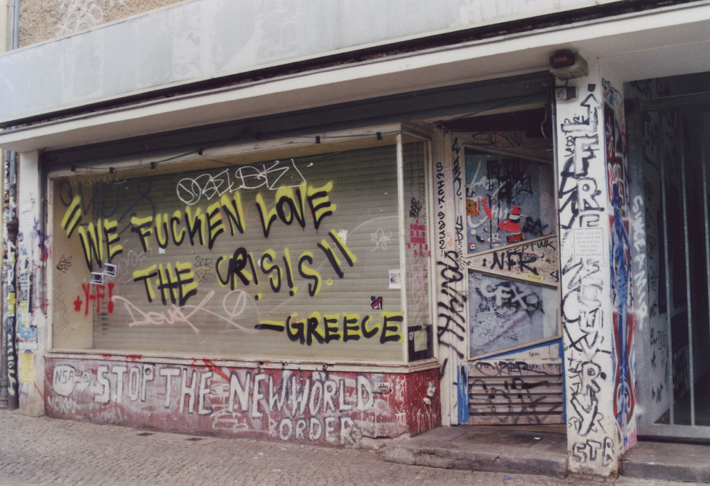 Graffiti an einem verrammelten Ladenfenster: We fucken love the Crisis. - Greece