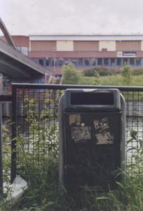 Ein Mülleimer mit mehren Aufklebern amn einem Kanal, im Hintergrund eine Brücke