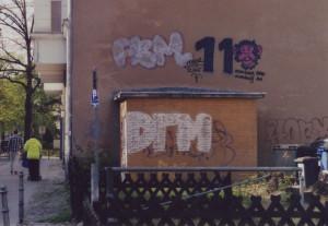 """Graffiti an einer Hauswand: Die Zahlen 11 - und dann als 0 ein Affenkopf, darunter der Schriftzug """"monkey see, monkey do"""""""