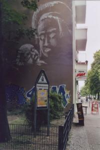 Wandbild an einer Brandmauer mit weisser Farbe: Silhouette einer Frau, die ein Baby in der Hand hält