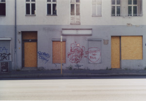 """Eine Hausfassade an einer breiten Strasse, die unteren Fenster sind mit Holz vernagelt, über die Hausfront ein Graffiti mit einem eher abstrakten Gesicht und dem Schriftzug """"Schönheit ist rauh"""""""