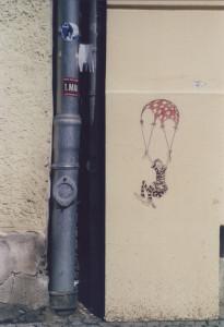 Street Art Daily Smile: Paste up eines Fallschirmspringers in Häftlingskleidung mit einem karierten Fallschirm