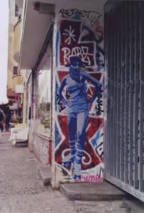 Street Art an einer Hofeinfahrt: Eine Frau mit Basecap, Sonnenbrille und Dreieckstuch vor dem Mund, auf Rollschuhen