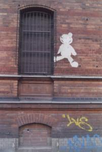 Street Art Paste up: Ein verblichener Teddy auf einer roten Backsteinmauer