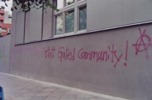 """Graue Neubauwand mit dem Schriftzug """"statt Gated Community"""" (Fortsetzung vom Bild gated1)"""